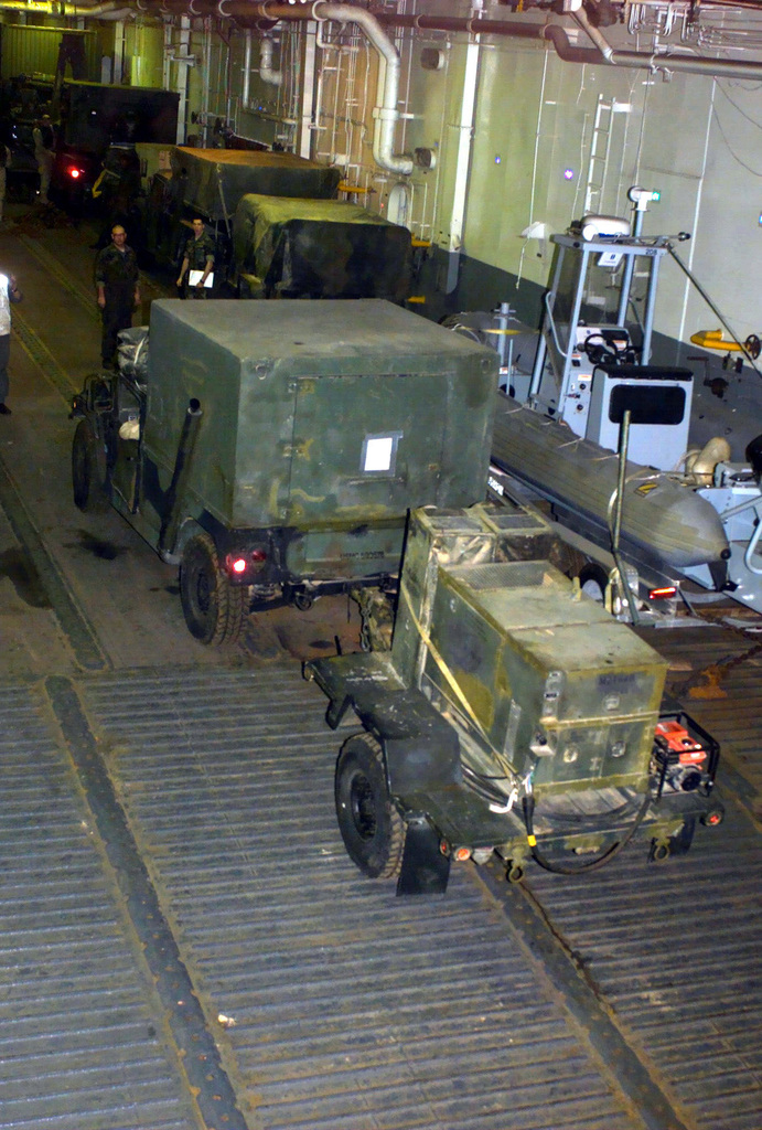 US Navy (USN) and US Marine Corps (USMC) personnel direct a High-Mobility Multi Purpose Wheeled Vehicle (HMMWV) equipped with a S-788/G Lightweight, Multipurpose Shelter (LMS), towing a portable trailer mounted generator, as equipment and supplies for Marines assigned to Battalion Landing Team, 2nd Battalion, 2nd Marines, 24th Marine Expeditionary Unit (MEU), Special Operations Capable (SOC), is offloaded from the well deck aboard the US Navy (USN) WASP CLASS: Amphibious Assault Ship, USS NASSAU (LAH 4), during Operation IRAQI FREEDOM