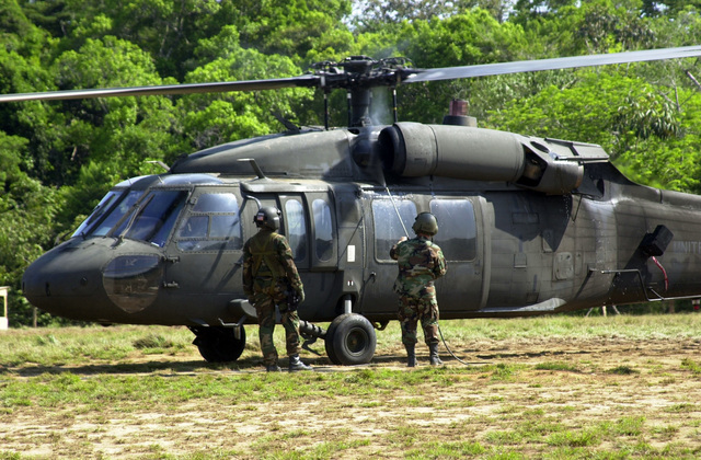 """U.S. Army SGT. Frederick Derry (left), Crew CHIEF, 150th General Support Aviation Battalion, New Jersey Army National Guard (NJANG), watches as another Soldier washes the UH-60 Blackhawk helicopter that just arrived from Panama City to the Joint Task Force Chiriqui Base Camp""""Amistad.""""the home of New Horizons 03, Las Lajas, Chiriqui Province, Panama, on March 29, 2003. (U.S. Army photo by Kaye Richey) (Released)"""