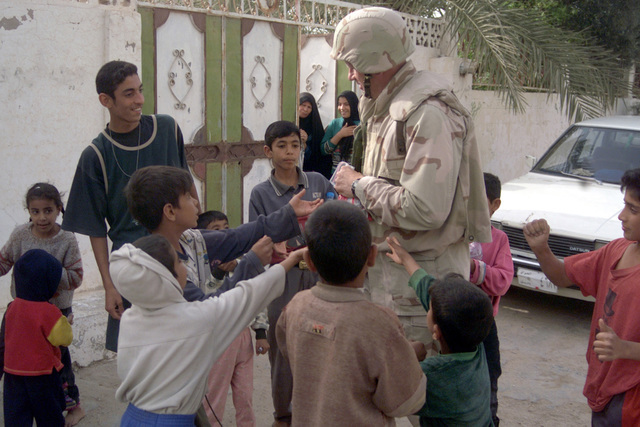 US Marine Corps (USMC) Lieutenant Colonel (LCT) Dave Long, assigned to the 1ST Marine Expeditionary Force (MEF), 3rd Civil Affairs Group (CAG), distribute candy to local Iraqi children, in the town of Umm Qasr, Iraq, during Operation IRAQI FREEDOM