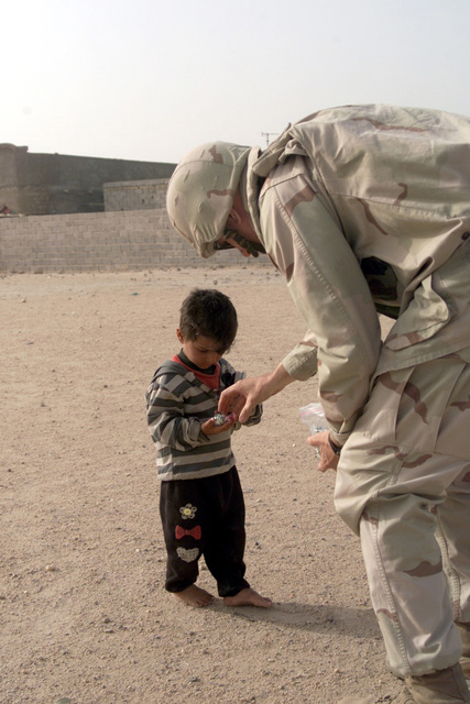 US Marine Corps (USMC) Lieutenant Colonel (LCT) Dave Long, assigned to the 1ST Marine Expeditionary Force (MEF), 3rd Civil Affairs Group (CAG) gives candy to a small Iraqi boy, in the town of Umm Qasr, Iraq, during Operation IRAQI FREEDOM
