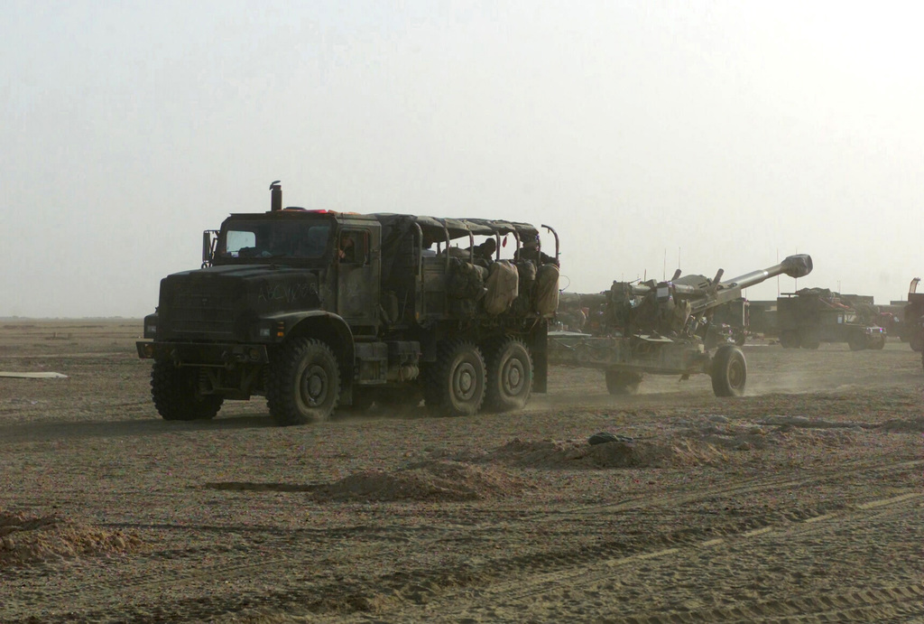 A US Marine Corps (USMC) MK-23 Medium Tactical Vehicle Replacement (MTRV) cargo truck is used to tow a M198 155mm towed howitzer, as Marines assigned to Battery/F, Battalion Landing Team, 2nd Battalion, 2nd Marines, 24th Marine Expeditionary Unit (MEU), Special Operations Capable (SOC), move out in a convoy of vehicles headed to an allied position in Iraq, during Operation IRAQI FREEDOM