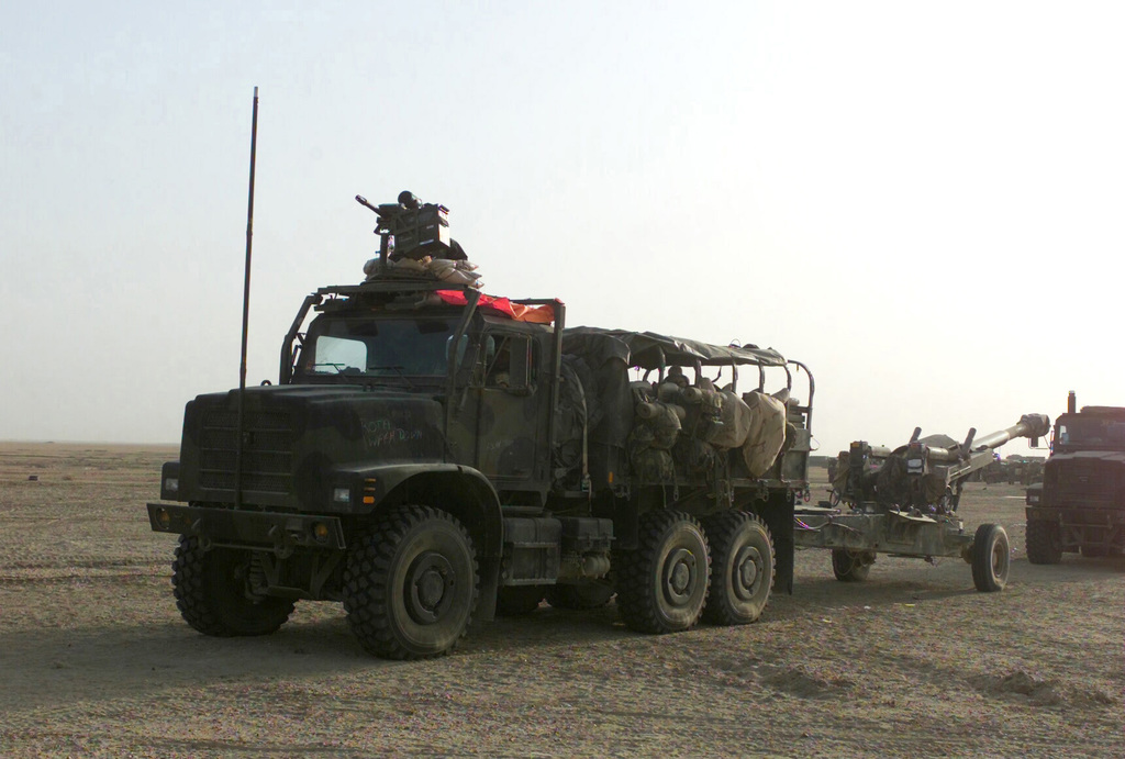 A US Marine Corps (USMC) MK-23 Medium Tactical Vehicle Replacement (MTRV) cargo truck equipped with a Mark 19 Mod 3, 40mm grenade machine gun mounted on top, is used to tow a M198 155mm towed howitzer, as Marines assigned to Battery/F, Battalion Landing Team, 2nd Battalion, 2nd Marines, 24th Marine Expeditionary Unit (MEU), Special Operations Capable (SOC), move out in a convoy of vehicles headed to an allied position in Iraq, during Operation IRAQI FREEDOM