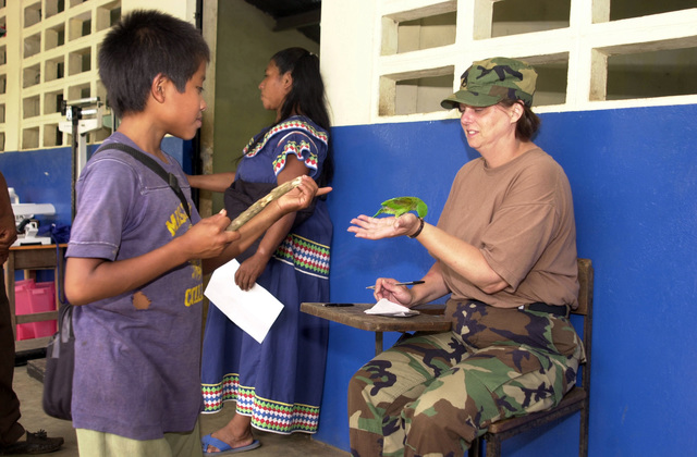 U.S. Army STAFF SGT. Gail Myers, Ohio Medical Command, Ohio Army National Guard (OHANG), lets a parakeet sit on her hand as a child looks on during a break at a Medical Readiness Training Exercise (MEDERTE) in Quebrada Guabo, Panama, on March 31, 2003, as part of New Horizons 03.  (U.S. Army photo by Miguel A. Negron) (Released)