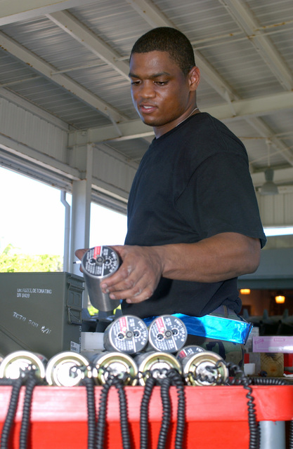 US Air Force (USAF) AIRMAN First Class (A1C) Edwin Evans, with the 40th Expeditionary Maintenance Squadron (EMXS), a munitions systems apprentice, prepares detonation fuses for aerial bombs, in support of Operation IRAQI FREEDOM