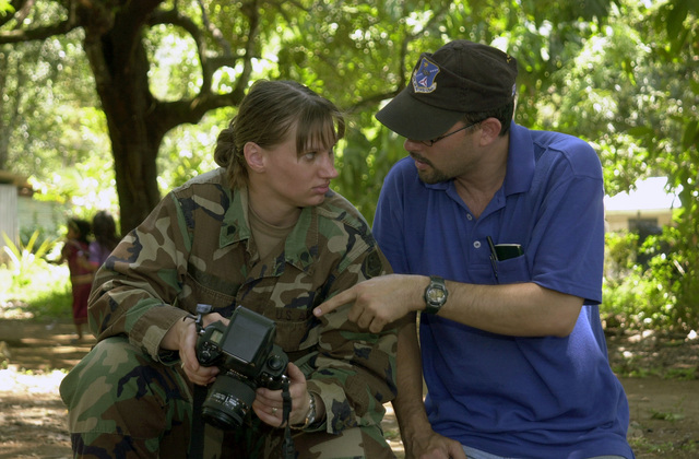 US Army (USA) Specialists (SPC) SPC Katherine Collins, 70th Mobile Public Affairs Detachment (MPAD) Missouri Army National Guard, confers with Miguel Negron, a Photographer assigned with the US Army South (USARSO) during a Medical Readiness Training Exercise, at Quebrada Guabo, Panama (PN), during Exercise NEW HORIZONS 2003