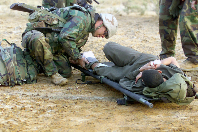 US Navy (USN) Hospital Corpsman Third Class (HM3) Travis P. Deel, from Haysi, Virginia, assigned to Charlie Company, 3rd Amphibious Assault Vehicle (AAV) Battalion, works on an injured enemy Prisoner Of War (POW), during a firefight in support of Operation IRAQI FREEDOM