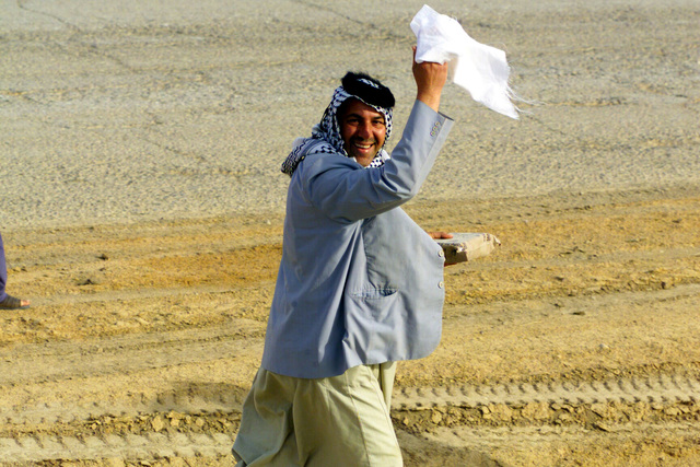 A happy Iraqi man surrenders holding a Meal Ready to Eat (MRE) in one hand and white cloth in the other just north of the An Nu'maniyah Bridge along Highway 27 in Iraq during Operation IRAQI FREEDOM. IRAQI FREEDOM is the multinational coalition effort to liberate the Iraqi people, eliminate Iraq's weapons of mass destruction and end the regime of Saddam Hussein