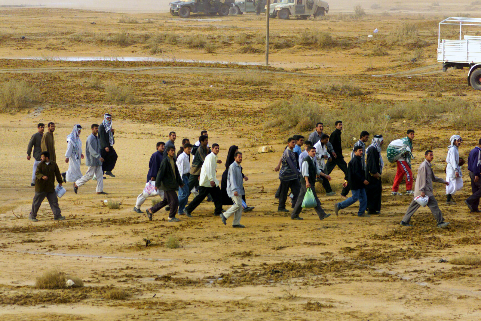 Iraqi Refugees walk across the intersection of Highway 27 and Highway 6, during Operation IRAQI FREEDOM