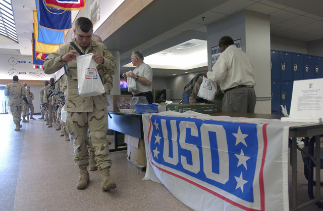 The United Service Organization (USO) distributes care packages to troops from the 37th Engineer Battalion (EB), Fort Bragg, North Carolina, during a refueling stopover at McGuire Air Force Base, New Jersey, in support of Operation IRAQI FREEDOM