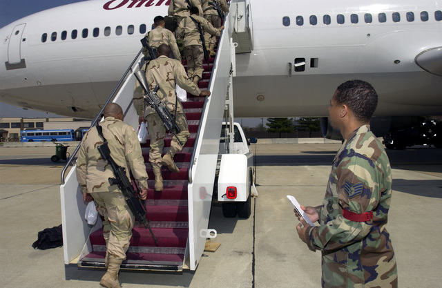 US Air Force (USAF) STAFF Sergeant (SSGT) Eric Bingham, oversees US Army (USA) troops from the 37th Engineer Battalion (EB), Fort Bragg, North Carolina, armed with FNMI 5.56mm M249 Squad Automatic Weapons (SAW) and other small arms, as the embark a contract aircraft after a refueling stopover at McGuire Air Force Base, New Jersey, in support of Operation IRAQI FREEDOM