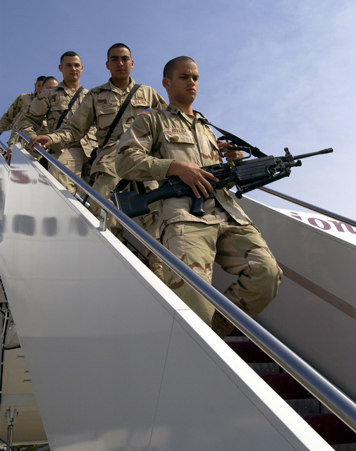 US Army (USA) troops from the 37th Engineer Battalion (EB), Fort Bragg, North Carolina, armed with FNMI 5.56mm M249 Squad Automatic Weapons (SAW) and other small arms, disembark an aircraft during a refueling stopover at McGuire Air Force Base, New Jersey, in support of Operation IRAQI FREEDOM