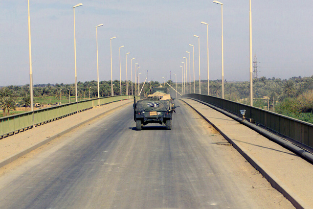US Marine Corps (USMC) personnel assigned to C/Company, 1ST Tank Battalion, drive a convoy across the Tigris River bridge along Highway 27 near An Numaniyah, Iraq, during Operation IRAQI FREEDOM