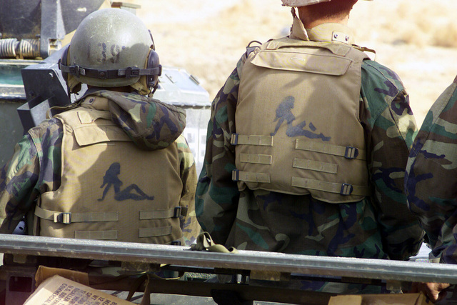 US Marine Corps (USMC) personnel with a design on their body armor wait along Highway 27 near An Numaniyah, Iraq, during Operation IRAQI FREEDOM