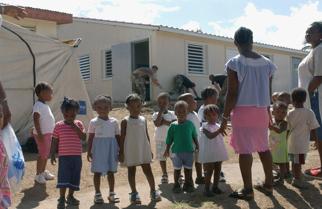 US Air Force (USAF) Civil Engineers (CE) with the 820th Red Horse Squadron (RHS), work concrete, creating a sidewalk at the Sandy Point Daycare Center construction site, while the future occupants of the Sandy Point Daycare Center come to watch during Exercise New Horizons, on the island of St. Kitts.  New Horizons is a US Southern Command (USSOUTHCOM) combined field-training exercise (FTX)