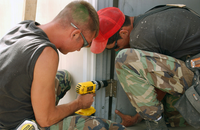 US Air Force (USAF) SENIOR AIRMAN (SRA) Josh Underdown, left and STAFF Sergeant (SSGT) Gregory Roger, with the 820th Red Horse Squadron (RHS), install a door at the Saint Paul's Health Center construction site on the island of St Kitts, during Exercise New Horizon.  New Horizons is a US Southern Command (USSOUTHCOM) combined field-training exercise (FTX)