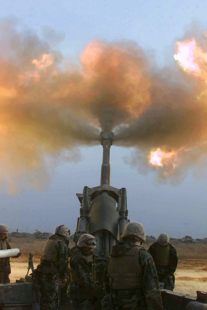 US Marine Corps (USMC) Marines assigned to Gun 2, L/Battery, 3rd Battalion, 11th Marine Regiment, fire their M198 155mm Howitzer towards Iraq, in support of Operation IRAQI FREEDOM
