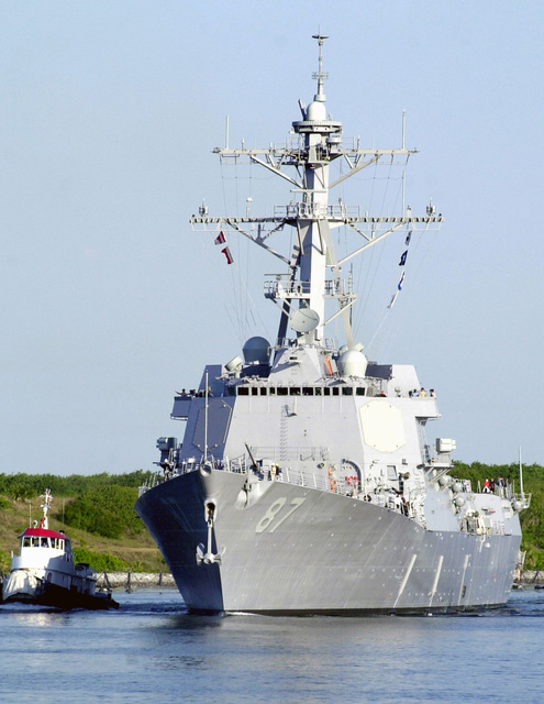 A port bow view of the US Navy (USN) ARLEIGH BURKE CLASS: (Flight IIA) Guided Missile Destroyer (Aegis), USS MASON (DDG 87), underway in the harbor at Port Canaveral, Florida (FL). A commercial tugboat is underway off the starboard side of the ship