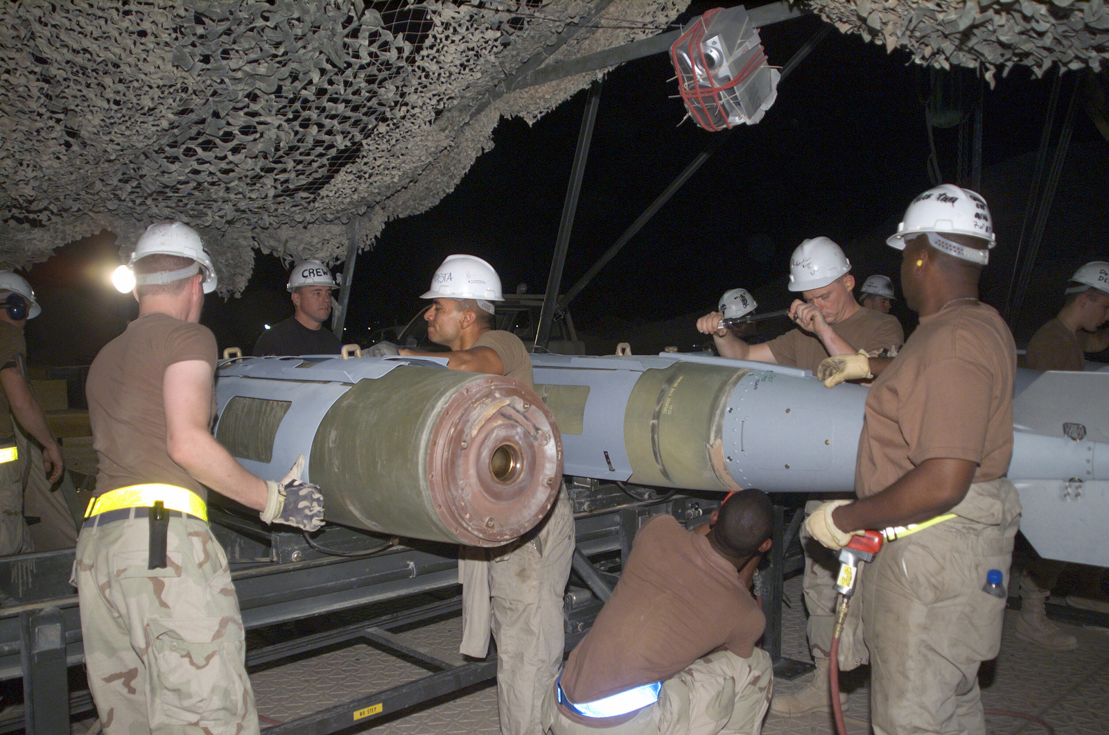 A US Air Force (USAF) team of munitions specialists from the 405th Expeditionary Munitions Squadron (EMS), install the fin assemblies to the Joint Direct Attack Munition (JDAM) bombs, in support of Operation IRAQI FREEDOM