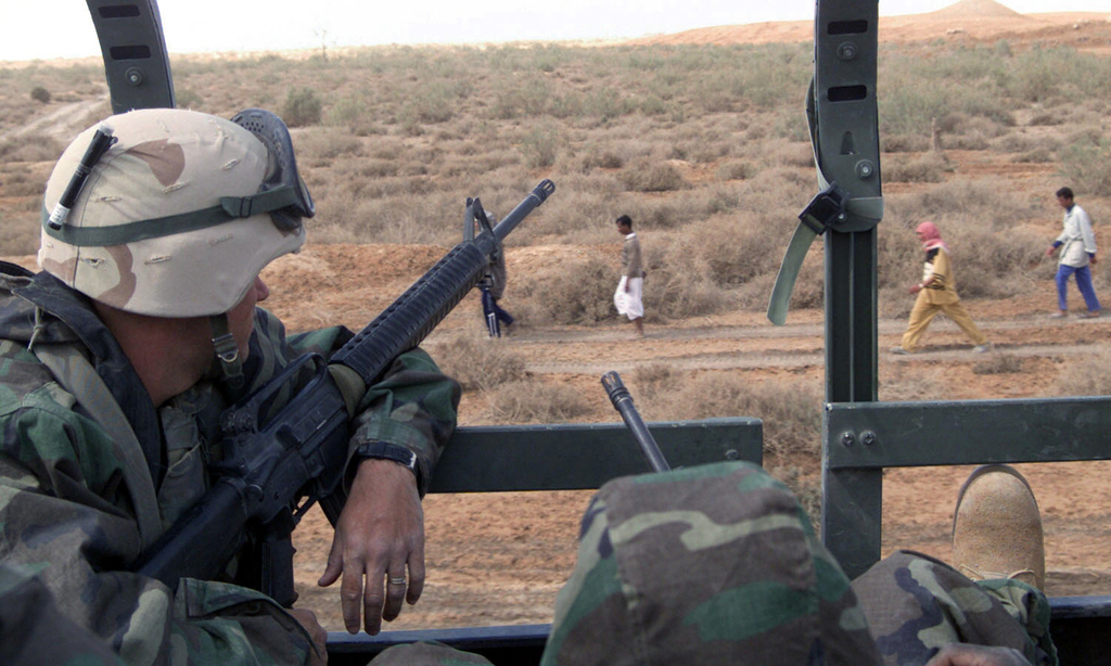 US Marine Corps (USMC) Lance Corporal (LCPL) James Ramsey, from Marine Wing Support Squadron-271 (MWSS-271), holds his Colt 5.56mm M16A2 Assault Rifle at the ready, as he watches Iraqi civilians walk down a road while providing security for a military convoy in support of Operation IRAQI FREEDOM