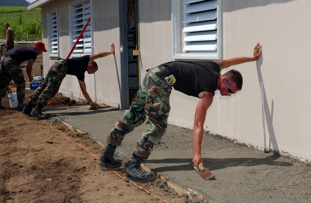 US Air Force (USAF) Civil Engineers (CE) with the 820th Red Horse Squadron (RHS) (RHS), work concrete to a smooth finish, creating a sidewalk at the Sandy Point Daycare Center construction site, while the future occupants of the Daycare Center come to watch, during Exercise New Horizons, on the island of St. Kitts. New Horizons is a US Southern Command (USSOUTHCOM) combined field-training exercise (FTX)