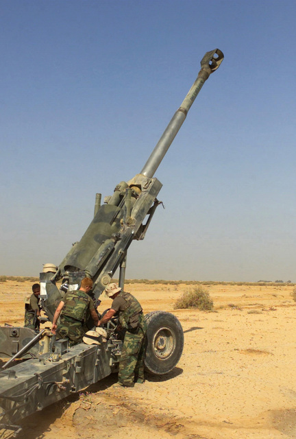 US Marine Corps (USMC) Marines assigned to F/Battery, Battalion Landing Team, 2nd Battalion, 2nd Marines, 24th Marine Expeditionary Unit (MEU), Special Operations Capable (SOC), check the maximum elevation their M198 155 mm towed howitzer at a gun position in Iraq, during Operation IRAQI FREEDOM