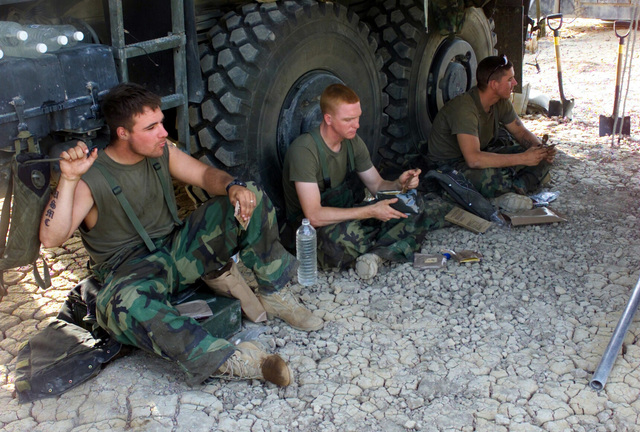 US Marine Corps (USMC) Marines assigned to F/Battery, Battalion Landing Team, 2nd Battalion, 2nd Marines, 24th Marine Expeditionary Unit (MEU), Special Operations Capable (SOC), enjoy a meal of Meals Ready to Eat (MRE) in the shade of their Medium Tactical Vehicle Replacement (MTVR) truck at a gun position in Iraq, during Operation IRAQI FREEDOM