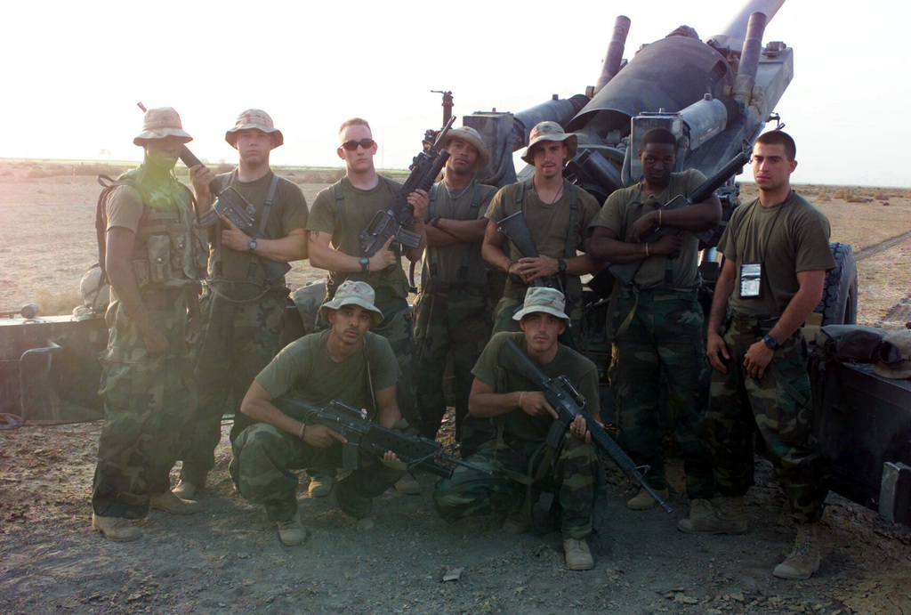 US Marine Corps (USMC) Marines assigned to F/Battery, Battalion Landing Team, 2nd Battalion, 2nd Marines, 24th Marine Expeditionary Unit (MEU), Special Operations Capable (SOC), poses for a group photograph in front of the M198 155mm towed howitzer gun position in Iraq, during Operation IRAQI FREEDOM