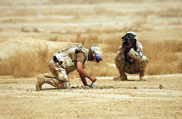 US Air Force (USAF) Technical Sergeant (TSGT) Marcos Coriano, a Videographer from the 1ST Combat Camera Squadron (CCS), documents British Royal Air Force (RAF) Corporal (CPL) Mav Dierking, an Explosive Ordnance Disposal (EOD) SPECIALIST from RAF Marham, as he digs up unexploded ordnance (UXO) found in the desert during a sweep of a forward area, in support of Operation IRAQI FREEDOM