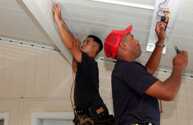 US Air Force (USAF) Civil Engineers (CE) STAFF Sergeant (SSGT) Anthiny Malvin, left and Technical Sergeant (TSGT) Darrell Johnson, with the 820th Red Horse Squadron (RHS), install lighting fixtures at the Sandy Point Daycare Center construction site, during Exercise New Horizons, on the island of St. Kitts. New Horizons is a US Southern Command (USSOUTHCOM) combined field-training exercise (FTX)