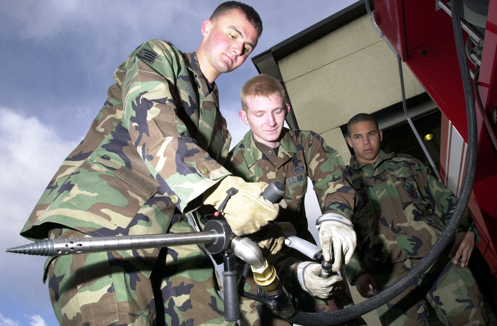 US Air Force (USAF) Fire Fighters STAFF Sergeant (SSGT) Michael Champion, left, AIRMAN (AMN) Jacob Norris, center and AIRMAN First Class (A1C) Emilio Cruz, all with the 31st Civil Engineer Squadron (CES), Fire Protection Flight, connect a Skin Penetrating Agent Application Tool (SPAAT) to a hose used in fighting aircraft fires