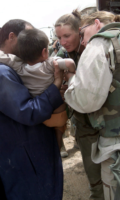 US Navy (USN) Hospital Corpsman First Class (HM1) Laurie Varner, left and HM1 Maureen Smith, examine an Iraqi child during a humanitarian visit to a village near Three Rivers, in support of Operation IRAQI FREEDOM