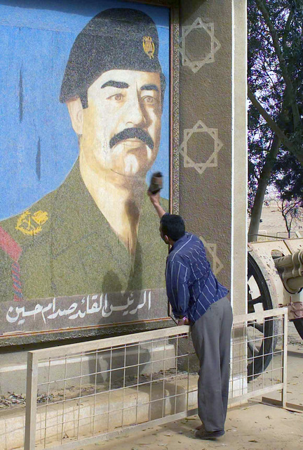 An Ar Rustamiyah Iraqi native takes his aggression out on one of the many large public murals of Saddam Hussein during Operation IRAQI FREEDOM