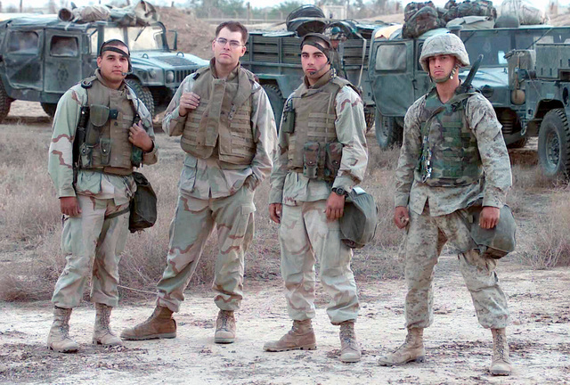 Posing for a picture are, 7th Marines Communications Company Combat Veterans, Sergeant (SGT) Jesus Delgado, left, from Dallas, Texas, Corporal (CPL) Marvan Davis, next, from Monterey, California, CPL Michael Mullins from Onsted, Michigan and CPL Anthony Murphy, right, from Portland, Oregon at Ar Rustamiyah, Iraq during Operation IRAQI FREEDOM