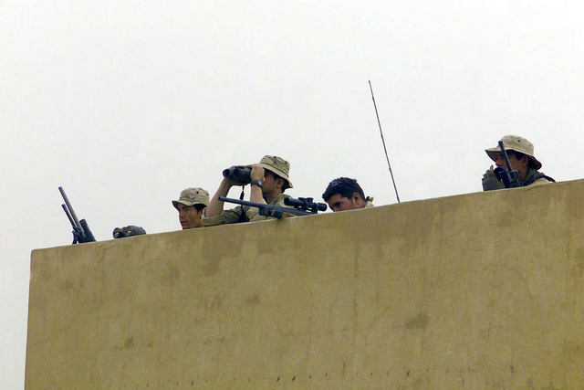 US Marine Corps (USMC) Scout Snipers with Charlie Company, 1ST Battalion, 5th Marines, 1ST Marine Division out of Camp Pendleton, California, secure a traffic control point 15 miles south of the presidential palace, in support of Operation IRAQI FREEDOM