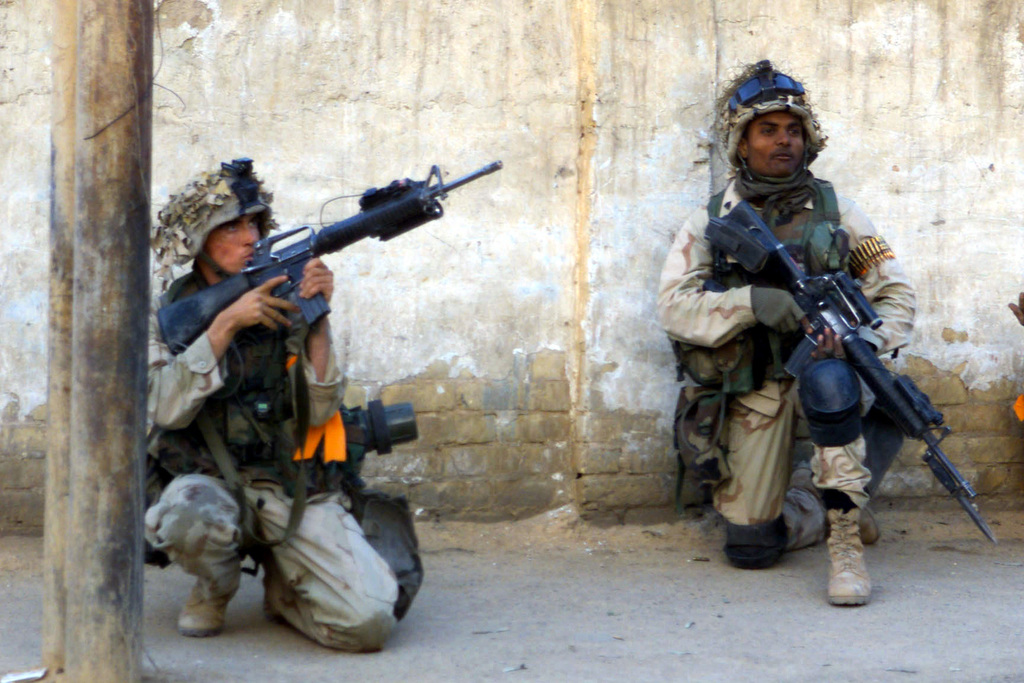 Two US Marine Corps (USMC) Marines assigned to C/Company, 1ST Battalion, 5th Marines, 1ST Marine Division, armed with 5.56mm M16A2 rifles work to clear the streets of Iraqi resistance on their way to their objective of securing Saddams Presidential Palace, during Operation IRAQI FREEDOM