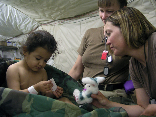 US Navy (USN) Hospital Corpsman Second Class (HM2) Sara Beishir (right) and Hospital Corpsman First Class (HM1) Jody Stenquist (standing) comfort a four-year old female Iraqi patient (left) who arrived at the USN Fleet Hospital Three (FH-3) Casualty Receiving center, Camp Viper, Iraq (IRQ), with a shrapnel wound to her right foot for initial treatment before being transferred to the USN Military Sealift Command (MSC) Mercy Class Hospital Ship, USNS COMFORT (T-AH 20) during Operation IRAQI FREEDOM
