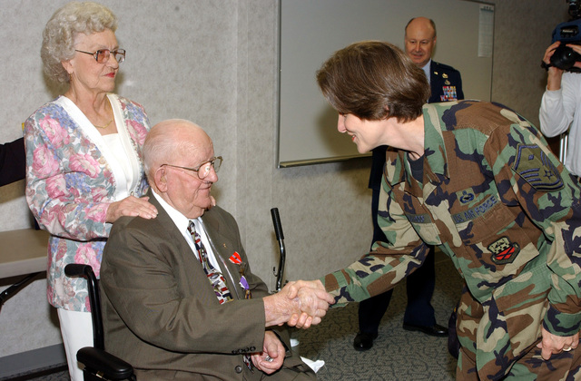 """World War Two (WWII) US Army (USA) Private First Class (PFC) William H.""""Dub""""Wilson Jr. (center), accompanied by his wife Idel, is congratulated by USAF MASTER Sergeant (MSGT) Elizabeth Bookhoop, First Sergeant, 165th Mission Support Flight, following an award ceremony held at the 165th Airlift Wing, Savannah International Airport (IAP), Georgia (GA). PFC Wilson was presented with various awards including the Bronze Star, the Purple Heart, and the Combat Infantryman Badge. The awards were presented fifty-seven years after he left the service"""