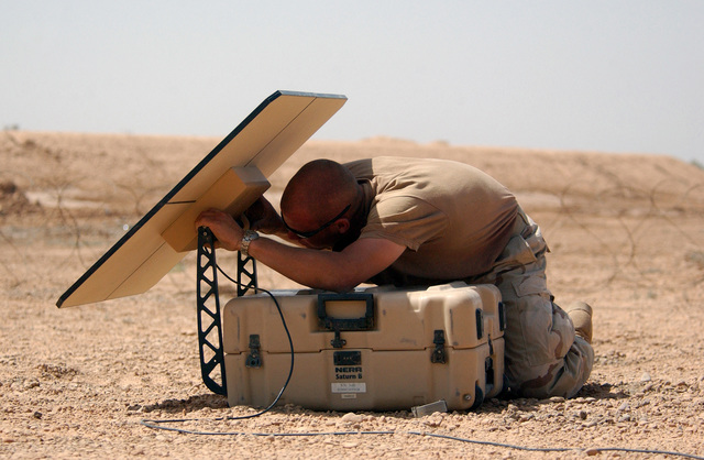 US Air Force (USAF) AIRMAN First Class (A1C) Joe Harvey, Satellite Communications Technician, for the Global Mobility Assessment Team (GAT), 621st Air Mobility Group, sets up an International Maritime Satellite (INMARSAT) at the Baghdad International Airport (IAP), in Iraq, during Operation IRAQI FREEDOM