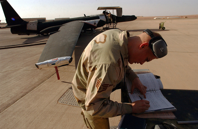 US Air Force (USAF) STAFF Sergeant (SSGT) Brian Spegal, Non-Commissioned Officer In Charge (NCOIC), 99th Aircraft Maintenance Squadron (AMXS), 363rd Expeditionary Aircraft Maintenance Squadron (EAMXS), signs off forms after completing maintenance on a USAF U-2R Dragon Lady aircraft while deployed with the at an undisclosed location in Southwest Asia, during Operation IRAQI FREEDOM