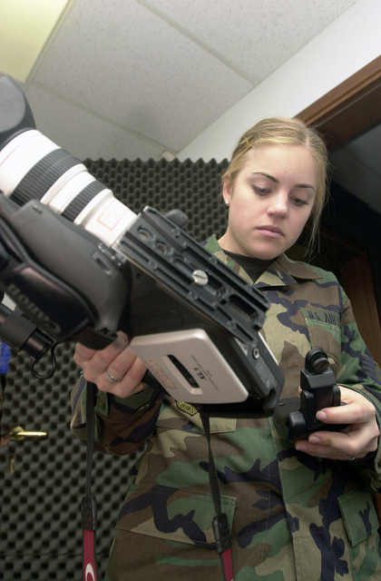 US Air Force (USAF) STAFF Sergeant (SSGT) Kelli Sabatino, Visual Imagery and Intrusion Detection (VIIDS) Journeyman, 31st Communications Squadron connects the optical image stabilizer to a digital video camera, following scheduled routine preventive maintenance at Aviano Air Base (AB), Italy