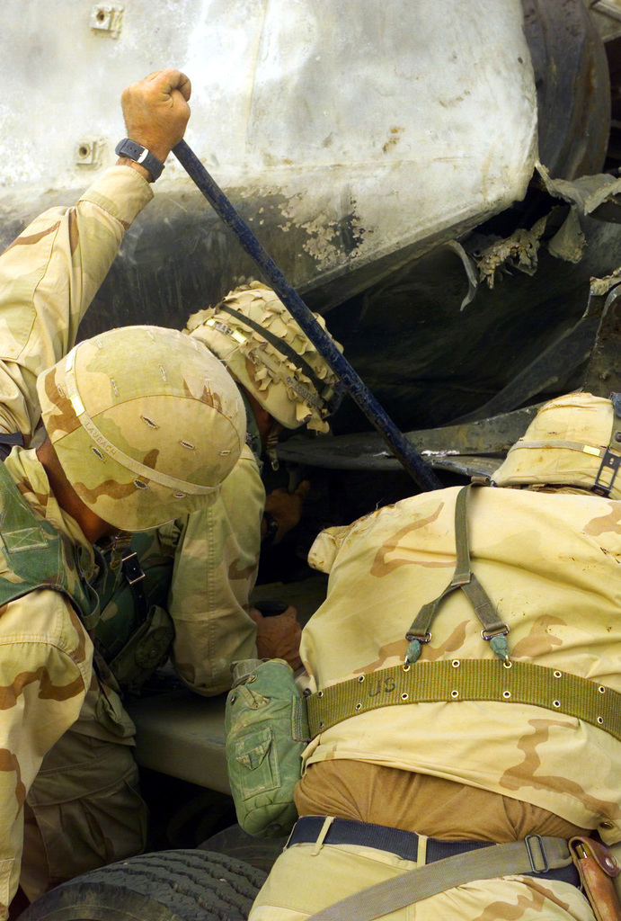 US Marine Corps (USMC) Marines assigned to Combat Service Support Battalion 18 (CSSB-18), and Marines assigned to Mortuary Affairs (MA), search the wreckage of a destroyed Amphibious Assault Vehicle (AAV7A1) for evidence of remains from Marines listed as Missing In Action (MIA), at an ambush site located within the city of An Nasariyah, Iraq, during Operation IRAQI FREEDOM