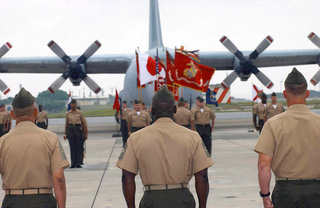 With a KC-130 Hercules as a backdrop, Sergeant Major (SGTMAJ) Roberto Orosco, USMC, (left), SGTMAJ Frankie Holmes, USMC, (center) and Colonel (COL) Gordon O'Neill, USMC, Commanding Officer, Marine Aircraft Group-36 (MAG-36), look on as the formation prepares for the pass in review. The review is part of the MAG-36 post and relief ceremony for the departing SGTMAJ Orosco and his relief, the oncoming SGTMAJ Holmes at Marine Corps Air Station (MCAS) Futenma, Okinawa, Japan