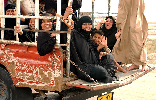 A group of local Iraqi women and children gesture to show support as a military convoy passes the vehicle in which they are riding, on the highway near the port of Umm Qasr Iraq, during Operation IRAQI FREEDOM