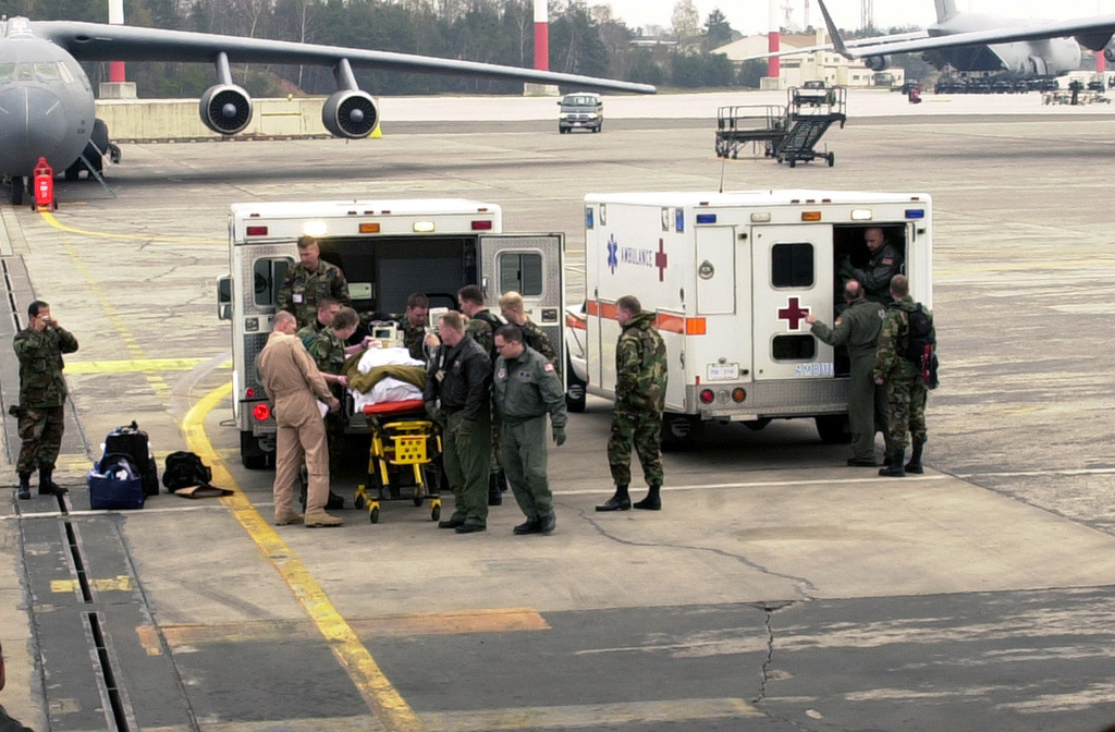 Joint Service US Military medical personnel assigned to the 452nd Aeromedical Staging Facility (ASF), offload litter patients from ambulances on the flight line at Ramstein Air Base (AB), Germany. Among the patients is US Army (USA) Private First Class (PFC) Jessica Lynch, 507th Maintenance Ordnance Company. The 452nd AFS provides support and emergency care to patients transiting through the Aeromedical Evacuation System