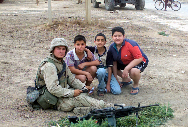 Private First Class (PFC) C. Renwick, USMC, C Company (C CO), 1ST Battalion (BN), 7th Marine Regiment (MAR REGT), spends time with some children of Ziona, the suburb of Baghdad. Combat Service Support Company (CSSC) 117, Regimental Combat Team 7 (RCT-7), 1ST Marine Division (MD) found suicide vests here during Operation IRAQI FREEDOM. Operation IRAQI FREEDOM is the multinational coalition effort to liberate the Iraqi people, eliminate Iraq's weapons of mass destruction and end the regime of Saddam Hussein