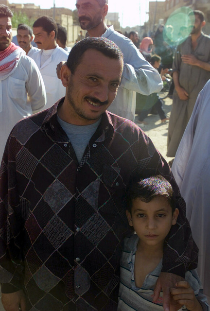 As an Iraqi father (right) watches, U S  Army SPC  Alexis