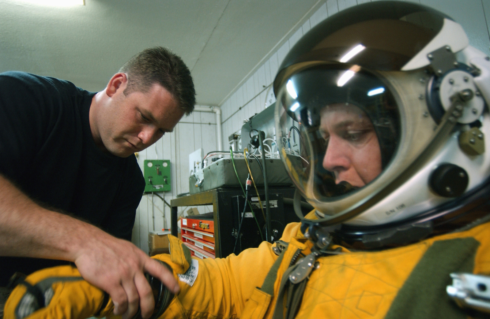 US Air Force (USAF) STAFF Sergeant (SSGT) Jeff Gilbert, physiological support division Technician assigned to the 9th Aircraft Maintenance Squadron, 363rd Expeditionary Aircraft Maintenance Squadron, assists USAF Major (MAJ) John Long, a U-2 Dragon Lady aircraft Pilot assigned to the 99th Reconnaissance Squadron, 363rd Expeditionary Reconnaissance Squadron, into his 1034 pressure suit in preparation for a mission in support of Operation IRAQI FREEDOM