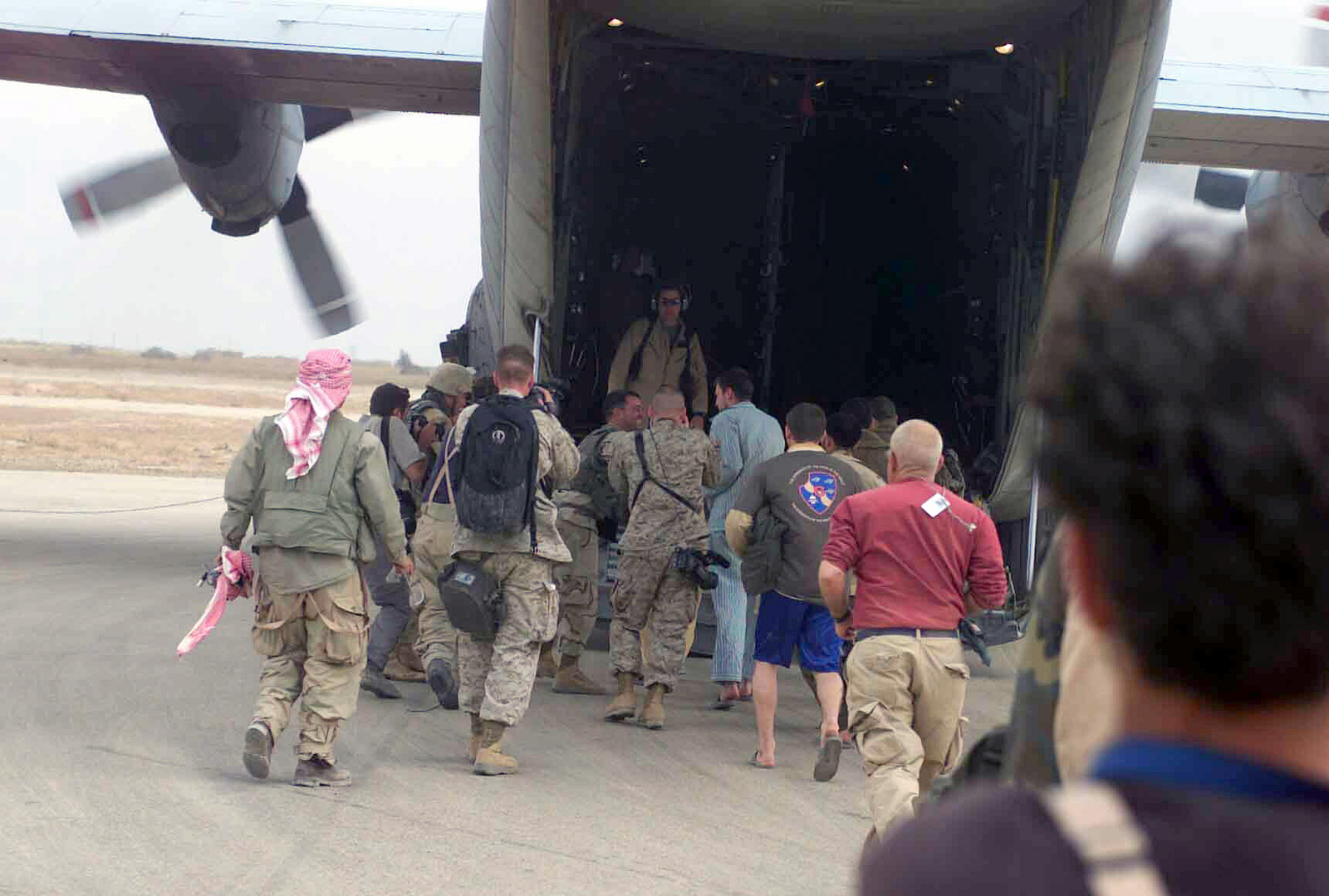 US Army (USA) CHIEF Warrant Officer (CWO) Ronald Young, (wearing striped blue pajamas) and USA Private First Class (PFC) Patrick Miller (green T-shirt and blue shorts) are congratulated by soldiers and photographed by members of the News Media as they board a US Air Force (USAF) C-130 Hercules aircraft at Logistical Support Area Chesty, 65-miles south of Baghdad, Iraq. COW Young and PFC Miller are two of seven America Prisoners of War (POW's) that were recovered safely by US Marine Corps (USMC) 3rd Light Armored Reconnaissance Platoon, 1ST Marine Expeditionary Force, during Operation IRAQI FREEDOM