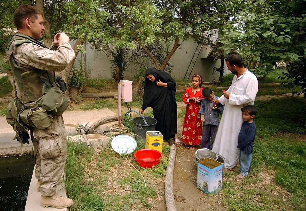US Marine Corps (USMC) Major (MAJ) Robert Carr, Civil Affairs SPECIALIST, 15th Marines Expeditionary Unit (MEU), Special Operation Capable (SOC), photographs of an Iraqi family getting water from a damaged water treatment facility located at An Nasariyah, Iraq, during Operation IRAQI FREEDOM