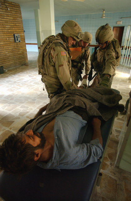 US Army (USA) Doctors assigned to Joint Task Force Four (JTF-4) checks the injuries of an Iraqi man inside the Yarmuk Hospital, located in Baghdad, Iraq. The man was found laying on a gurney with shrapnel wounds and multiple fractures to his arms and legs and without food and water for two days. USA Soldiers assigned to the 96th Civil Affairs Battalion and Joint Task Force Four (JTF-4) were conducting a survey of the hospital to assess damage done by looting, during Operation IRAQI FREEDOM